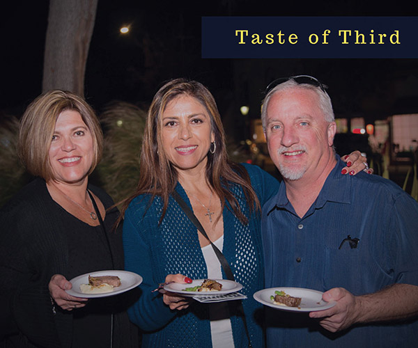 taste of third event picture. 3 people holding different food samples, happy. Evening setting, they are standing outside.