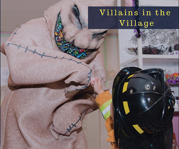 Villains in the village picture. Dressed up child as a fireman is shaking a hand of a person dressed as a goast.