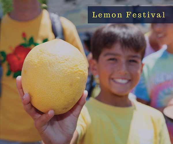 Lemon festival picture. young boy holding a lemon, with a big smile. Other youth in the background.