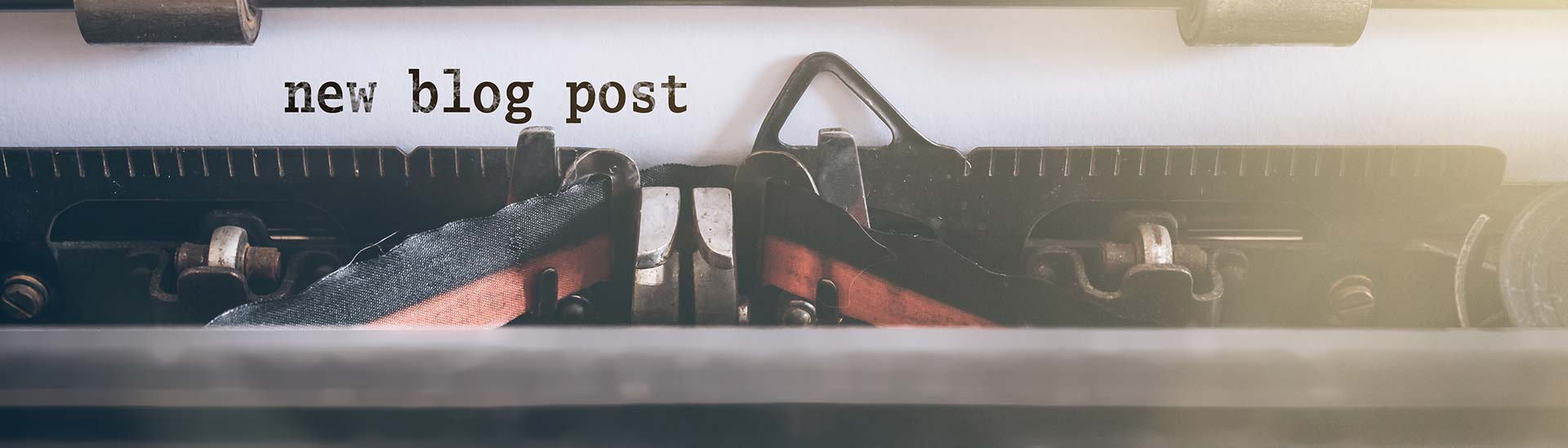 """The picture of old typewriter. """"new blog post"""" typed out on the white paper."""